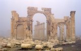 """Palmyra was an ancient city in Syria. It was an important city in central Syria, located in an oasis 215 km northeast of Damascus and 180 km southwest of the Euphrates at Deir ez-Zor. It had long been a vital caravan city for travellers crossing the Syrian desert and was known as the Bride of the Desert. The earliest documented reference to the city by its Semitic name Tadmor, Tadmur or Tudmur (which means """"the town that repels"""" in Amorite and """"the indomitable town"""" in Aramaic) is recorded in Babylonian tablets found in Mari."""